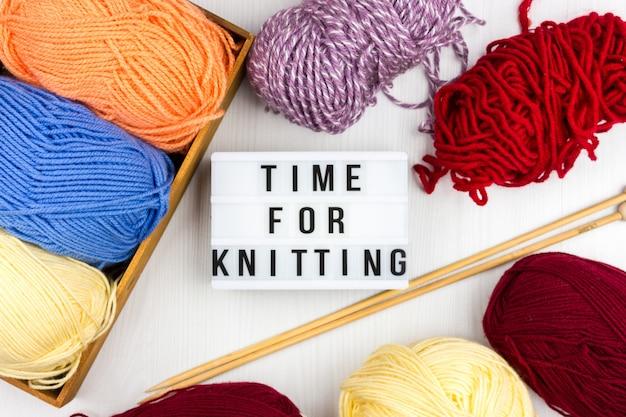 Flatlay von mehrfarbigen stricksträngen und stricknadeln mit schriftzug - zeit zum stricken