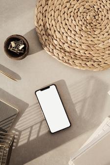 Flatlay von smartphone mit leerem bildschirm, notizbüchern, clips in holzschale, strohhalm auf beiger betonoberfläche
