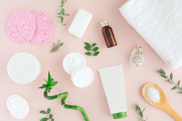 Flatlay von spa-kosmetik mit bambus, salz für bad, creme und handtuch auf pastellrosa