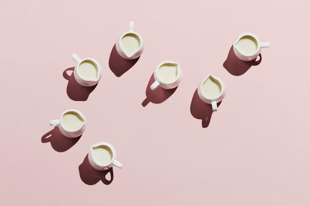 Flatlay von weißen cremes mit hafermilch auf pastellrosa hintergrund