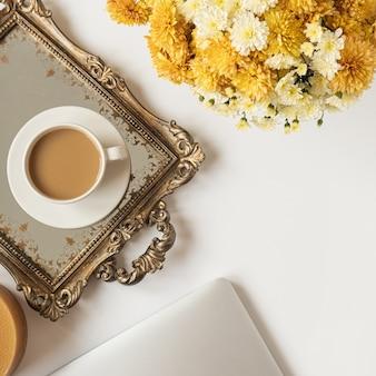 Flatlay weiblicher minimaler arbeitsbereich mit laptop, kaffeetasse und schönem blumenstrauß auf weißem tisch. draufsicht