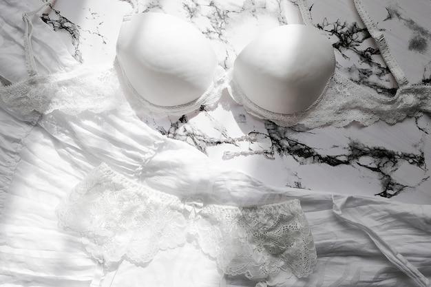 Flatlay-zusammensetzung mit weißem bh auf marmorhintergrund