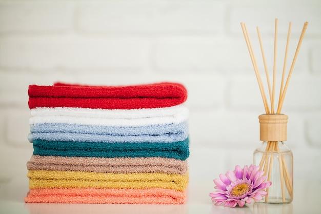 Flaumige badetücher auf hellem holztisch mit aromastöcken
