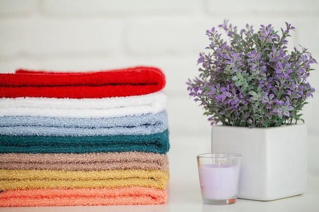 Flaumige badetücher auf hellem holztisch mit kerze