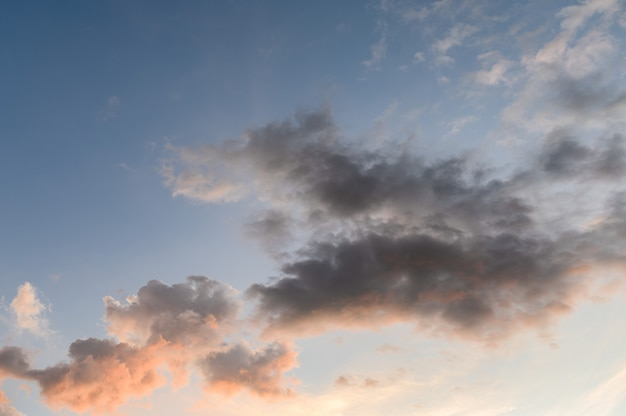 Flaumige dunkle wolken mit sonnenschein im himmel