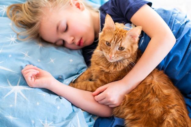 Flaumige katze des ingwers mit kleinem schlafendem mädchen auf dem blauen bett