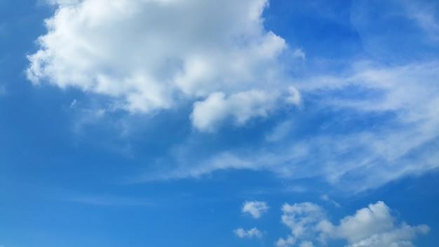 Flaumige wolken im hintergrund des blauen himmels