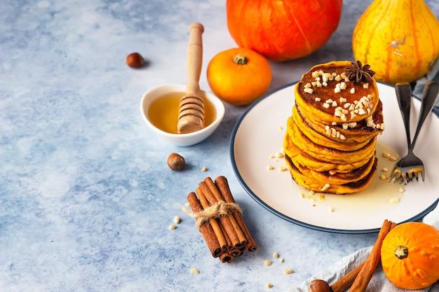 Flauschig würzige kürbispfannkuchen mit honig und nüssen, frischen kürbissen und gewürzen.