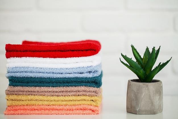 Flauschige badetücher auf hellem holztisch mit dekor und weißem hintergrund.