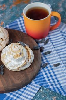 Flauschige baisermuffins mit schwarzen trockenen trauben auf dem tisch mit einer tasse tee.