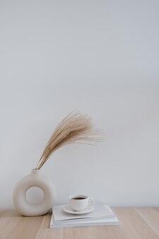 Flauschiges pampasgrasrohr in stilvoller vase, kaffeetasse und zeitschriften gegen weiße wand