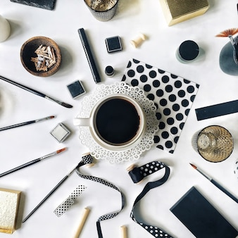 Flay lag arbeitsbereich home office mit schwarzer kaffeetasse, skizzenbuch, servietten, bändern, pinseln auf weiß