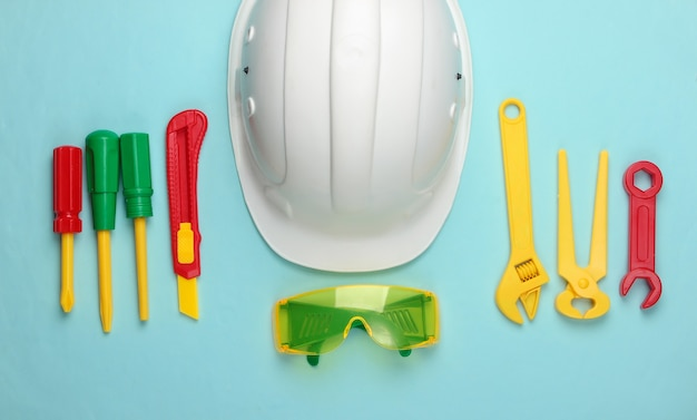 Flay lag komposition von kinderarbeitswerkzeugen und helm auf blau. ingenieur, baumeister. kindheitskonzept