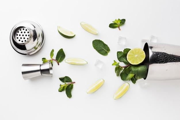 Flay lay von cocktail essentials mit shaker und limettenscheiben