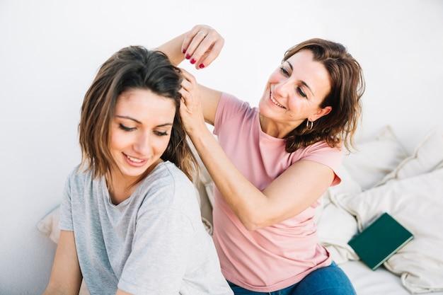 Flechtendes haar der frau der frau auf sofa