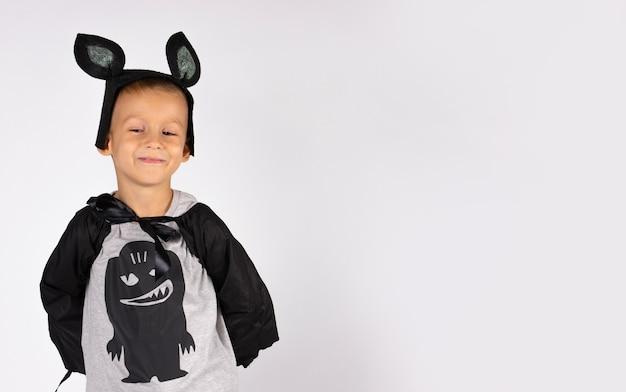 Fledermausjunge im karnevalskostüm, netter charakter. lächelnder junge, der auf eine weiße wand mit leerem raum herabblickt.