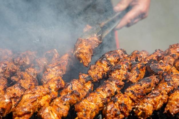 Fleisch am spieß auf dem grill im freien gebraten, sichtbare hände des kochs.