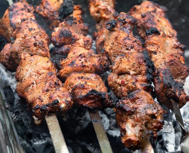 Fleisch am spieß. marinierter schaschlik, der auf einem grillgrill über holzkohle zubereitet wird. appetitanregendes fleisch am spieß gegrillt. schaschlik kochen. schweinefleisch auf kohle grillen