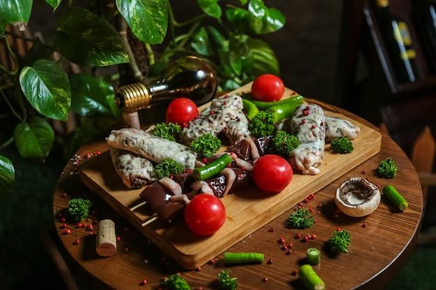 Fleisch auf dem holzbrett mit tomaten, pilzen und pfeffer mischen