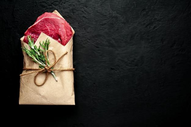 Fleisch aus einer metzgerei, in papier eingewickelt. ein stück rindfleisch auf einem betonschwarz