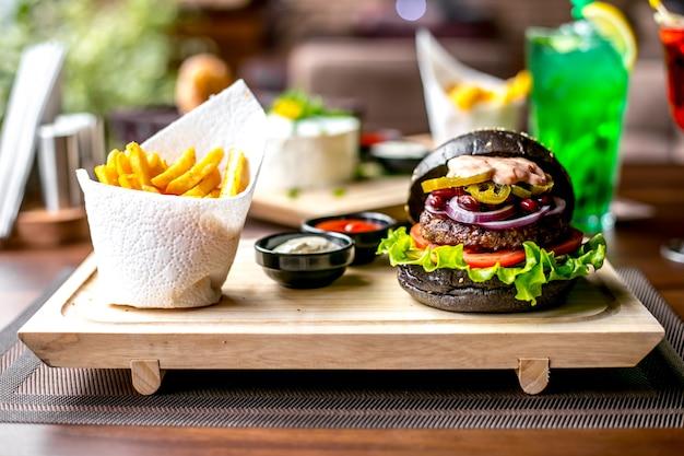 Fleisch burger salat tomaten zwiebel jalapenos bohnen pommes frites seitenansicht