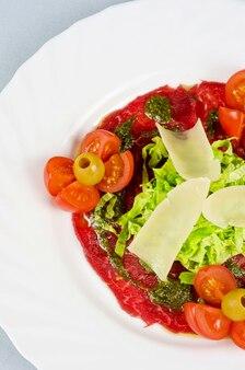 Fleisch carpaccio aus rindfleisch, parmesan, oliven, tomaten, sauce pesto