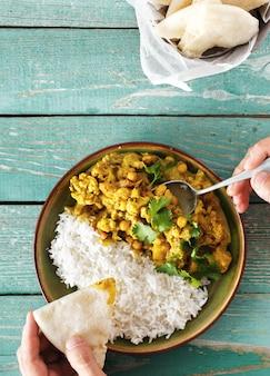 Fleisch fressende draufsicht naan brot des würzigen curryreises des blumenkohls