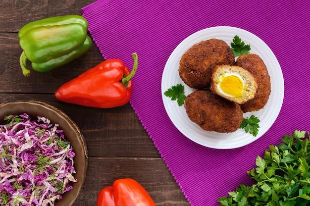 Fleisch mini-brötchen mit gekochtem ei auf dunklem holz. die draufsicht.