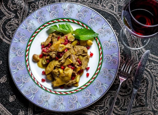 Fleisch mit gebackenen apfelzwiebeln granatapfelkastanien paprika draufsicht