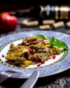 Fleisch mit gebackenen apfelzwiebeln granatapfelkastanien paprika seitenansicht
