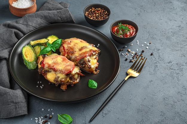 Fleisch mit gemüse und käse mit einer beilage aus zucchini auf dunkelgrauem hintergrund. seitenansicht, platz zum kopieren.