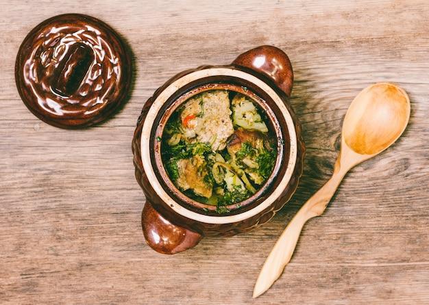 Fleisch mit kartoffeln in einem tongefäß und in einem hölzernen löffel auf tischplatteansicht