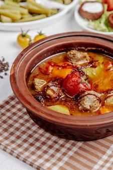 Fleisch mit kartoffeln und tomaten in einem tontopf