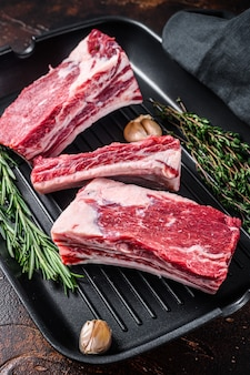 Fleisch mit kurzen rippen vom rinderkalb in einer grillpfanne, die zum kochen bereit ist. dunkler hintergrund. draufsicht.
