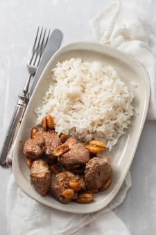 Fleisch mit nüssen und gekochtem reis auf weißem teller auf keramiktisch