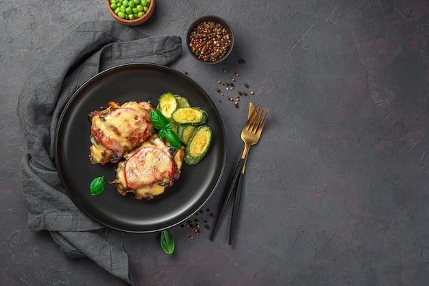 Fleisch mit pilzen, tomaten und käse mit einer beilage aus jungen zucchini auf dunkelgrauem hintergrund. ansicht von oben, kopienraum.
