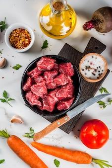 Fleisch, rindfleisch. frisches rohes gehacktes gulasch, rindfleischwürfel in einer schüssel. gewürze (salz, pfeffer), tomaten, knoblauch, zwiebeln. auf einem weißen marmortisch mit einer fleischgabel und einem messer. ansicht von oben