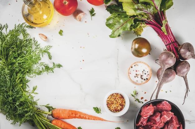 Fleisch, rindfleisch. frisches rohes gehacktes gulasch, rindfleischwürfel in einer schüssel. gewürze (salz, pfeffer), tomaten, knoblauch, zwiebeln. auf einem weißen marmortisch mit einer fleischgabel und einem messer. draufsichtkopienraum