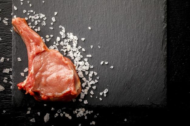 Fleisch-rohes frisches hammelfleisch auf dem knochen auf einem schiefer