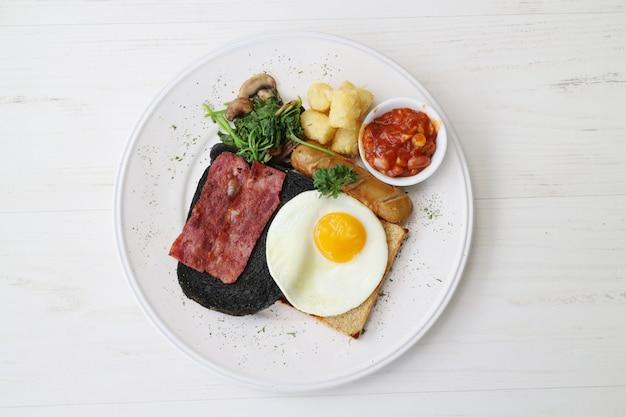 Fleisch steak mit ei, brot, wurst und gemüse