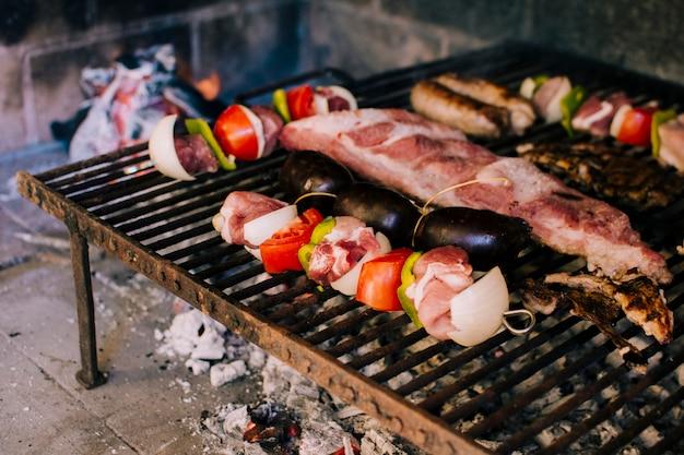 Fleisch und gemüse auf heißen kohlen grillen
