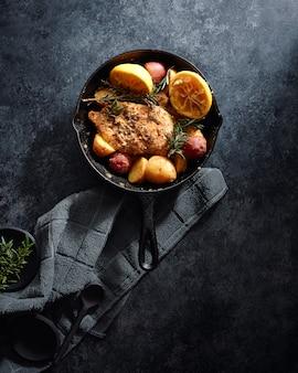 Fleisch und gemüse in einem schwarzen topf auf einer schwarzen oberfläche