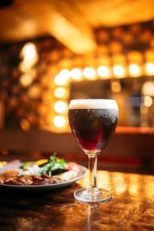 Fleisch- und gemüsegericht mit einem glas dunklem fassbier mit verschwommenen lichtern