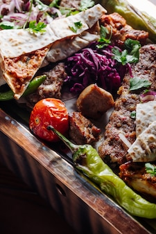 Fleisch- und gemüsegrill mit lavash und kräutern.