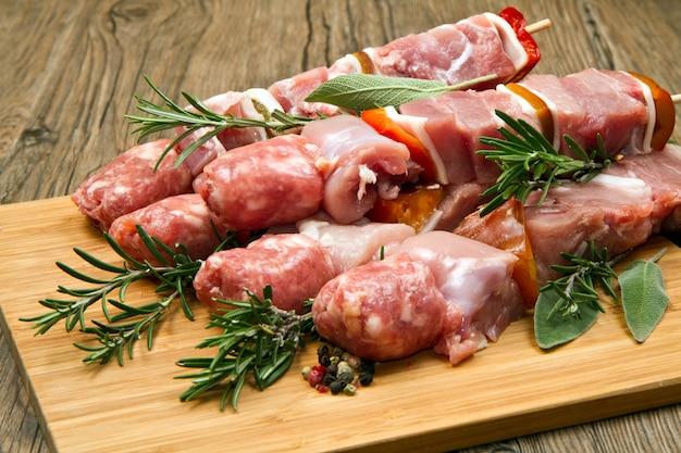 Fleisch- und pfefferaufsteckspindeln auf einem hölzernen schneidebrett