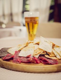 Fleisch und pommes auf einem holzteller mit bier.