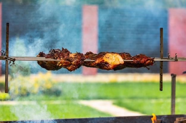 Fleisch vom schweinefleisch bereitet sich auf einer aufsteckspindel auf dem feuer im yard im sommer vor. rauch verleiht fleisch eine pikante note