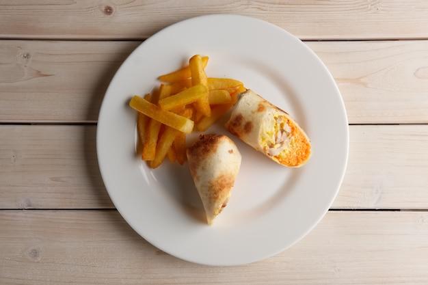 Fleisch, würzige karotten, kohl und käse in dünnem fladenbrot aufgerollt