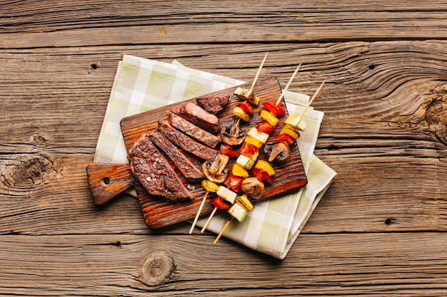 Fleischaufsteckspindel und gebratene steakscheibe auf hölzernem schneidebrett