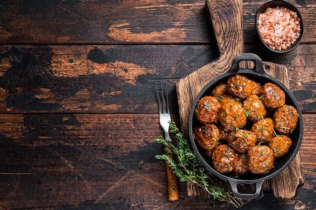 Fleischbällchen aus rind- und schweinefleisch mit thymian in einer rustikalen pfanne